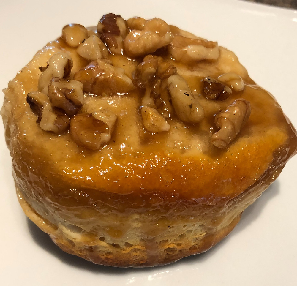 A close up of a sticky, glazed biscuit with pieces of chopped walnuts on top.