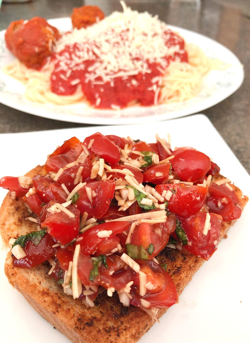 A slice of toasted bread is loaded with red ripened tomatoes, flakes of white cheese and slivers of green basil.  A plate of spaghetti and meatballs sits in the background.
