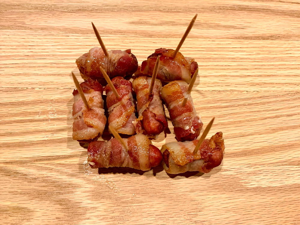 Eight small bacon wrapped sausages sit with toothpicks on a wooden surface, glistening with a sweet looking glaze. Toothpicks project from each bite-size appetizer.