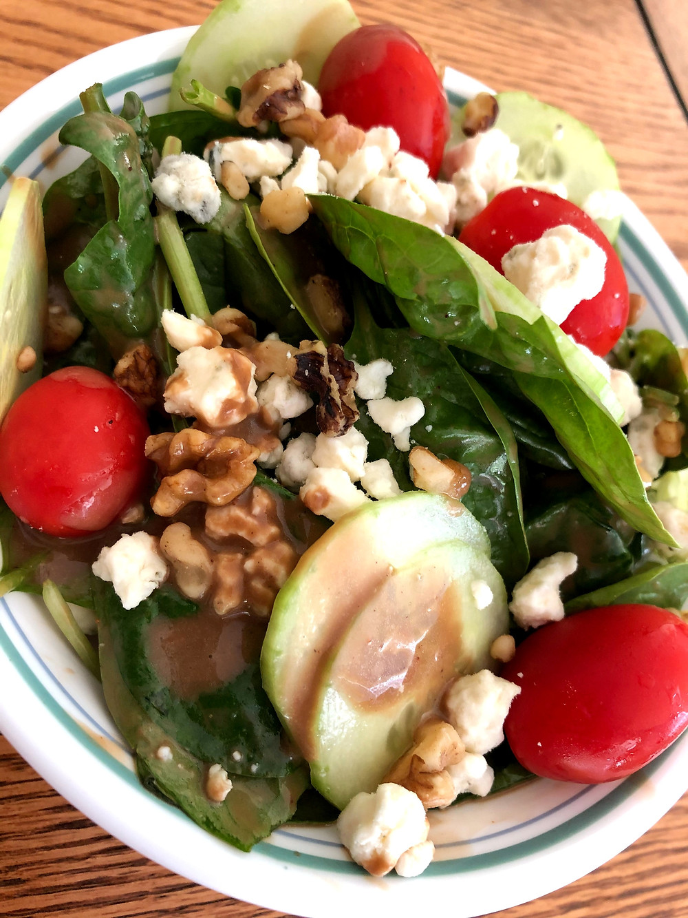 A closer photo of fresh green spinach, cucumbers, tomatoes, walnuts, cheese and brown dressing in bowl.