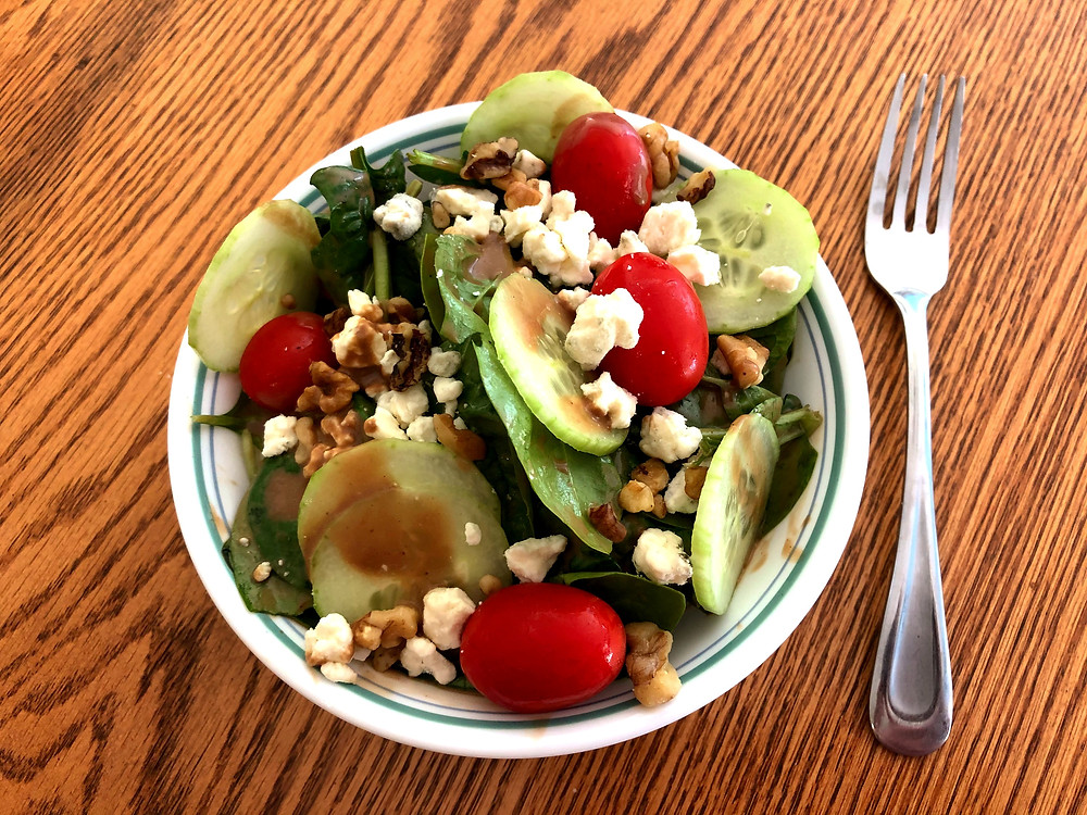 A bowl of green spinach, sliced cucumbers, cherry red tomatoes, brown chopped walnuts and crumbles of white cheese sit on a brown wooden table. A silver fork sits beside the bowl on the table.  A brown dressing is applied to the top of the fresh salad.