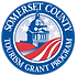 "Blue emblem with white text on outside edge reading ""Somerset County Tourism Grant Program"" Inside circle there is drawing o Somerset County Courthouse with red and white lines in front representing U.S. flag. Official logo of Somerset County Tourism Grant Program"