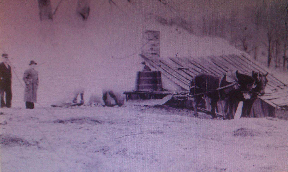Black and white photo of two men standing outside of small wood structure with chimney and two horses harnessed to pull a sled with buckets.
