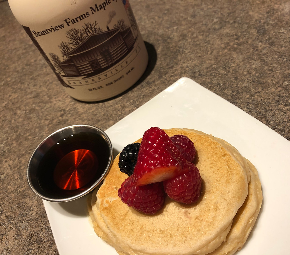 "A stack of flapjacks sits on a white plate, topped with red strawberry, red raspberries and a blackberry. A silver cup of amber colored syrup sits next to the pancakes. In the background a brown jug labeled ""Brantview Farms Maple"" sits."