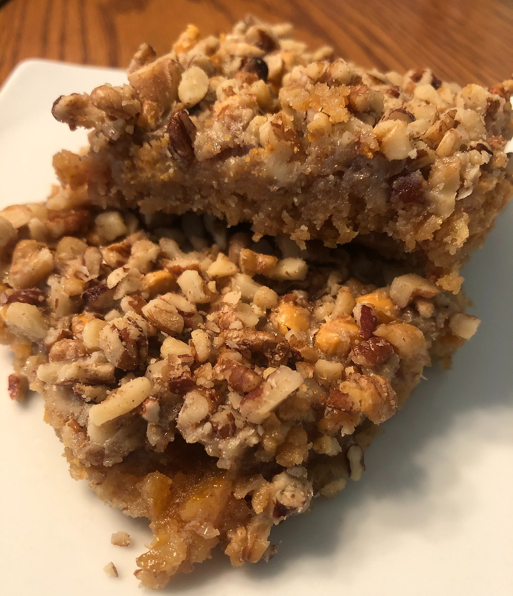 A close up of two brown cookie bars coated in nuts with a pale brown creamy caramel middle layer and flaky brown cookie crust.