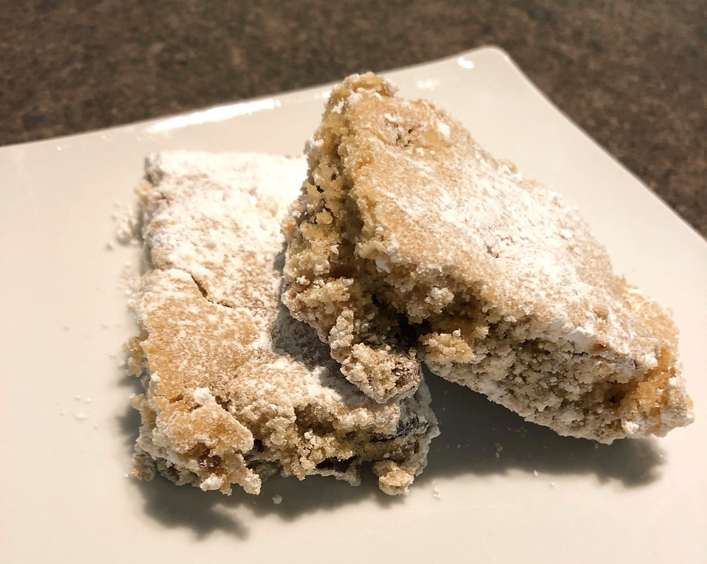 Two cake or cookie-like bars sit on white plate. They are dusted with white powdered sugar and appear to have pieces of nuts baked into them.