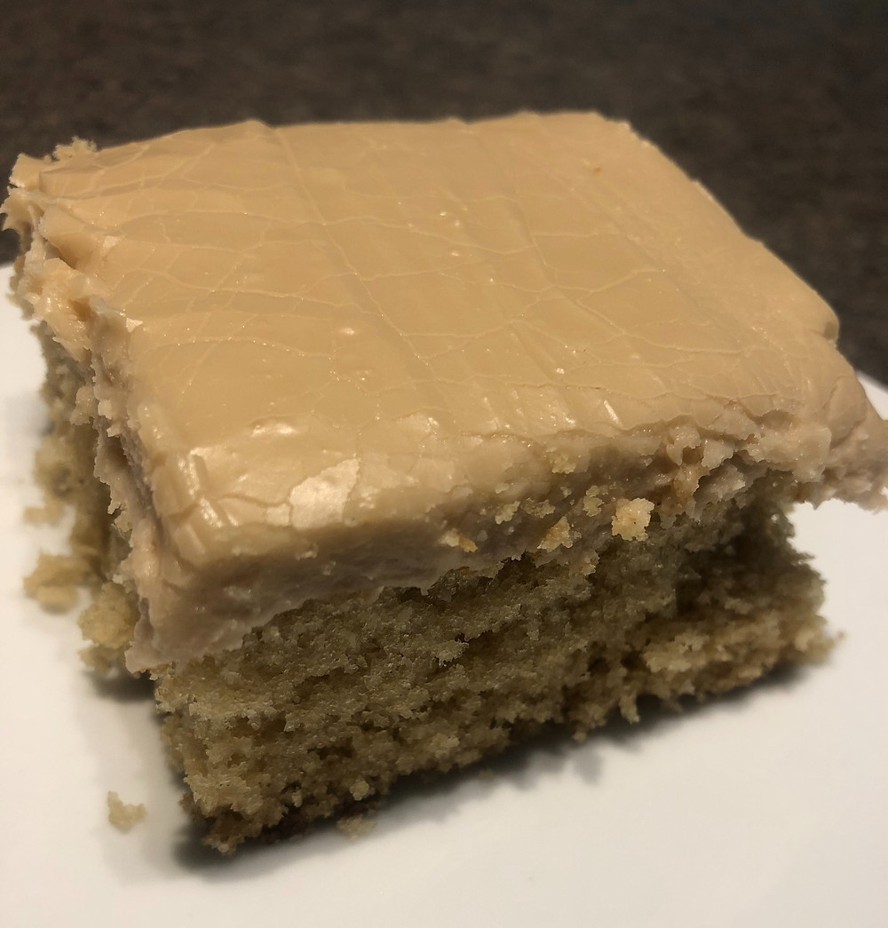 A light tan square piece of cake sits on a white plate, topped with creamy, tan-colored, thick frosting
