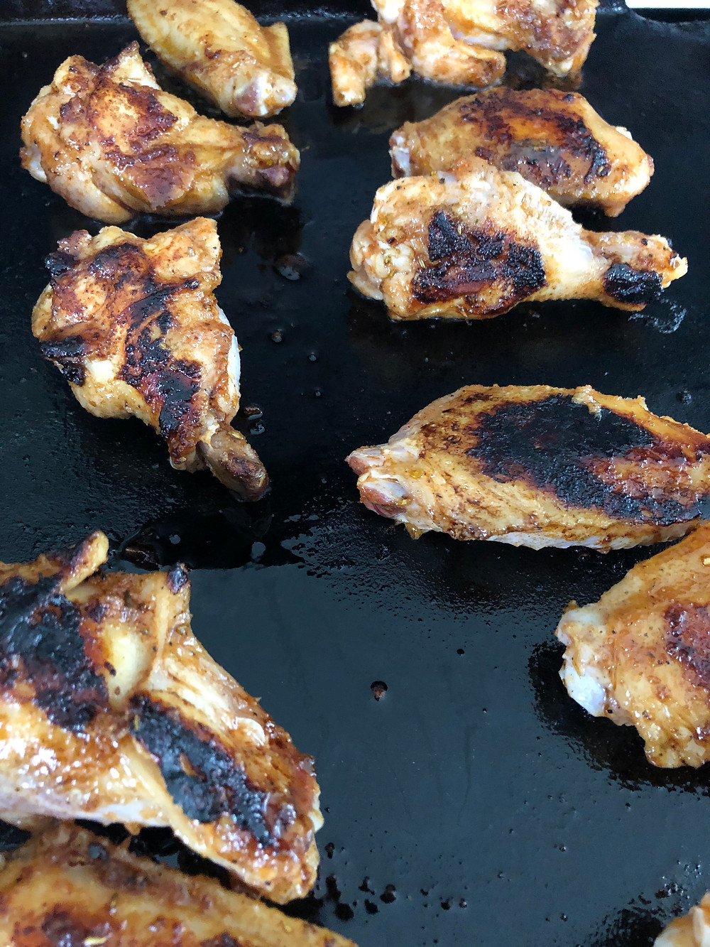 Seasoned chicken wings with a brown and black charred coat, cook on a black griddle.