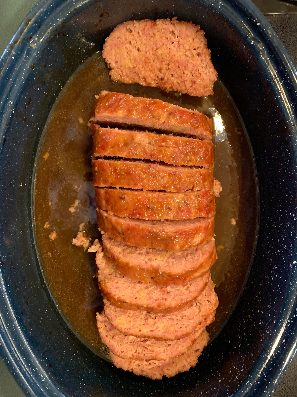 The loaf of meat is cut into inch wide pieces inside the black cooking pot.