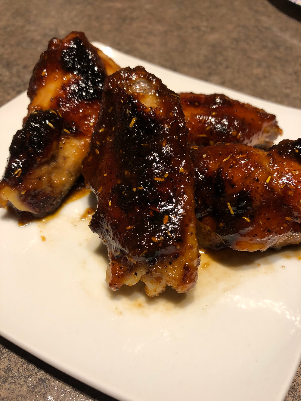 Glazed, saucy chicken wings with visible grill charring and herbs sit on a white plate, juices surrounding them.