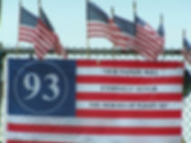 "A red white and blue flag with the large numer ""93"" in a circle of stars and the words ""Our Nation Will Eternally Honor The Heroes of Flight 93"" American Flags surroun the large flag."