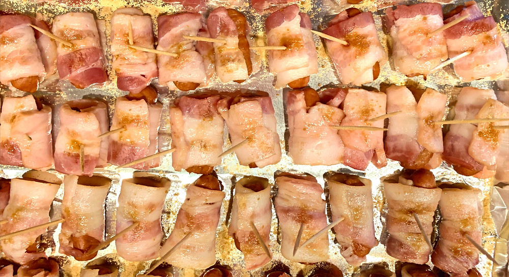 Rows of tiny sausages wrapped in bacon and secured with toothpicks line a foil covered tray.
