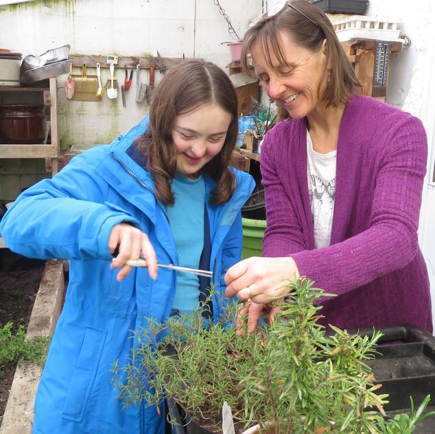 Sarah working with Maria to cut herbs.jpg