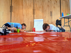 Children writing on cushions on the floor