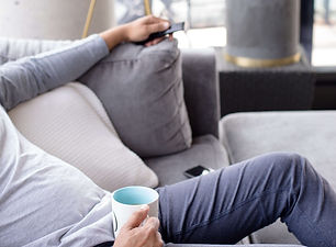 person-leans-back-on-a-grey-couch-while-holding-a-mug (1).jpg