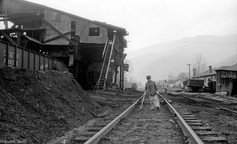 Young boy on crutches next to coal tipple