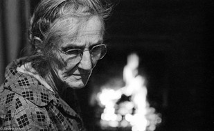 Frank Quillen's mother sitting in front of a fire