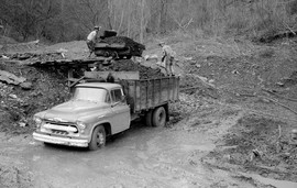 Dumping coal from doghole mine into truck.