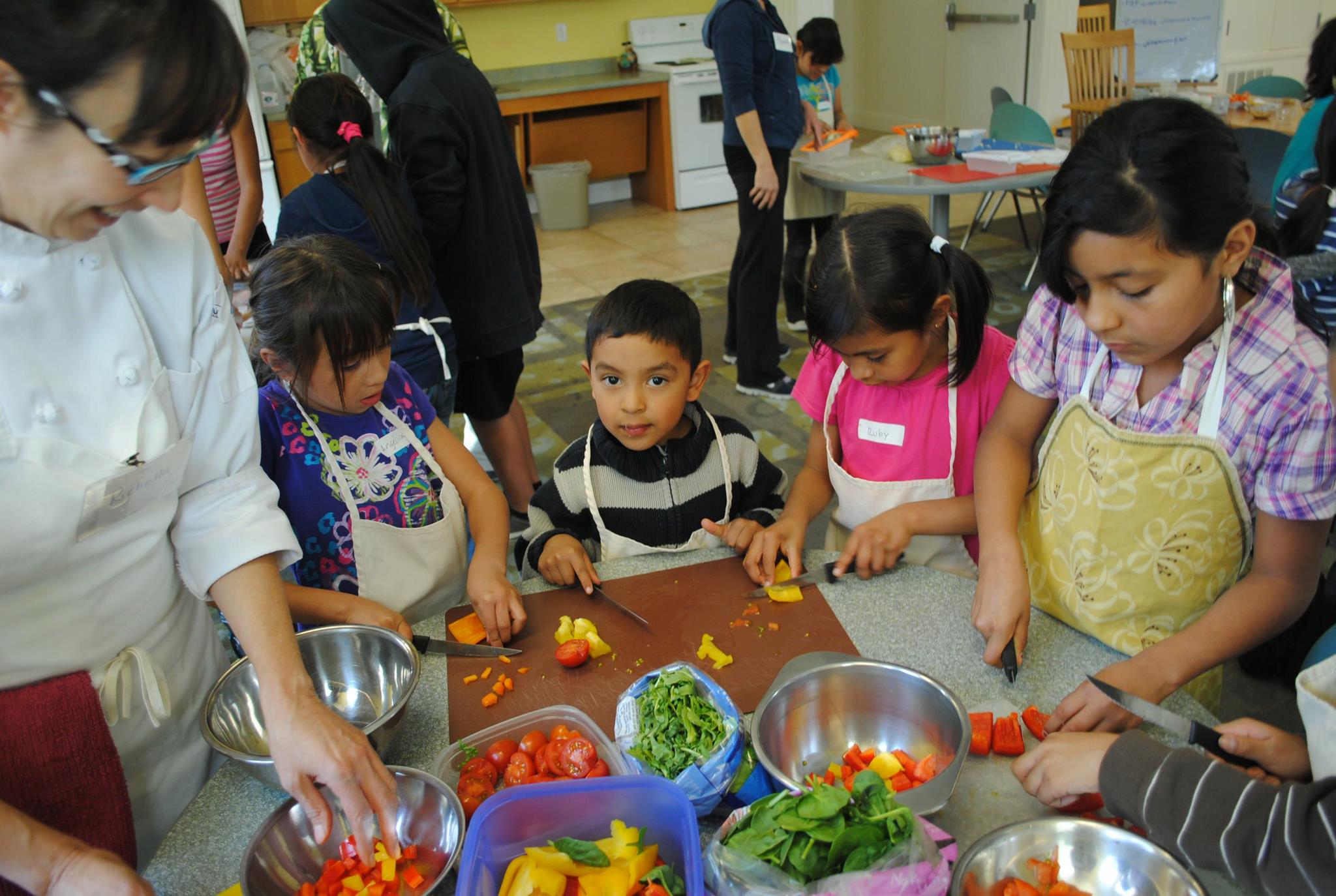 4 kids learning about nutrition in a classroom with a teacher