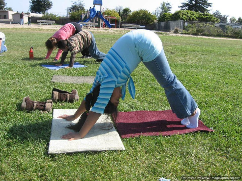 3 kids doing yoga on a lawn of grass