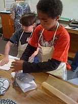 Two young boys cooking in a cooking clss