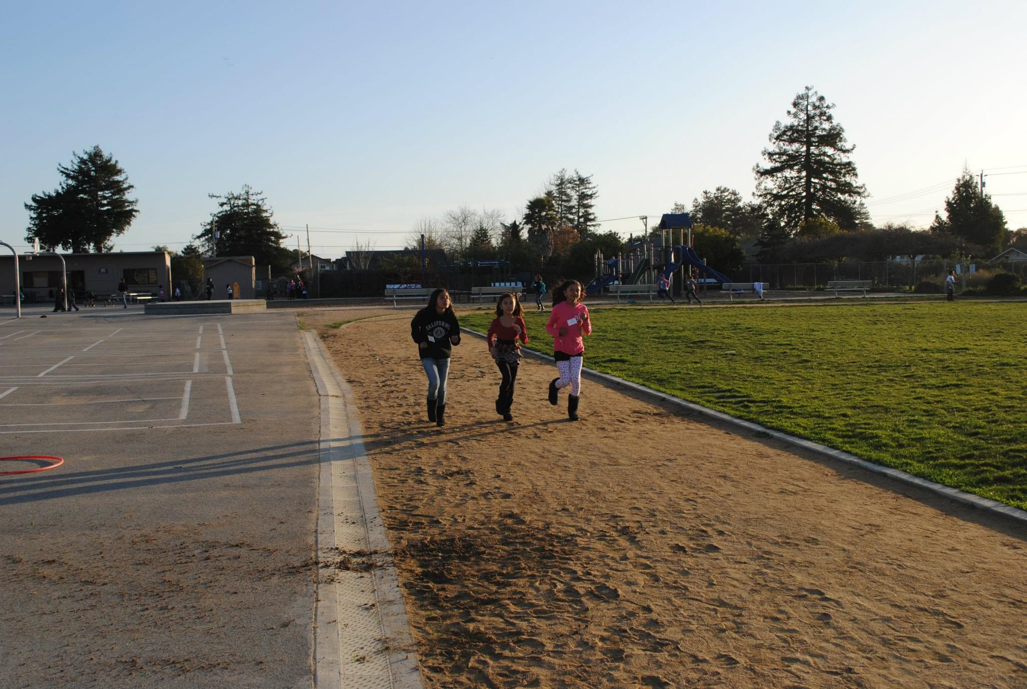 3 kids running the track at a school together