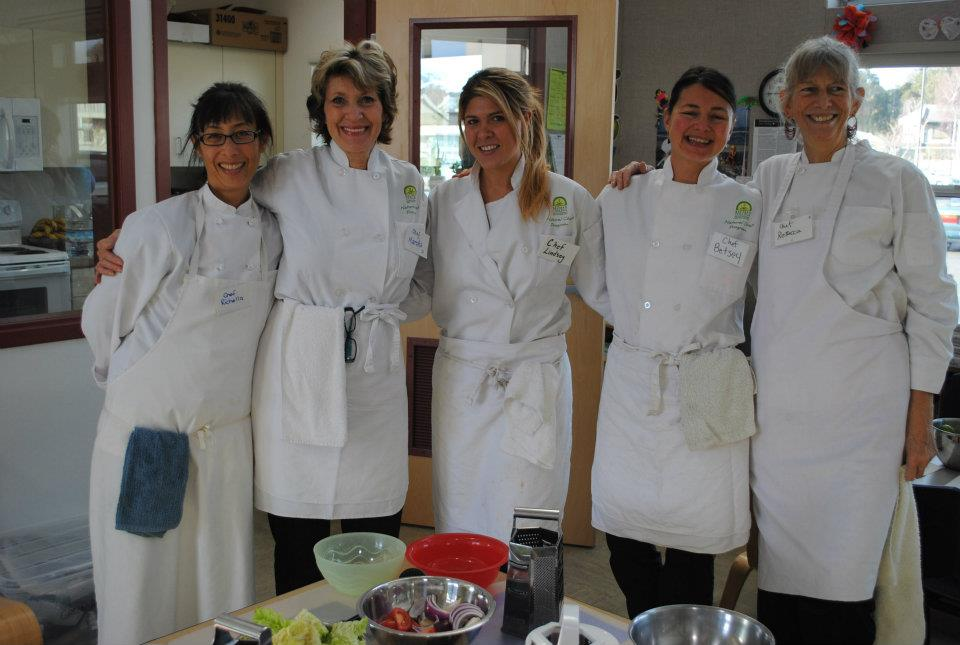 5 nutrition education teachers wearing culinary outfits smiling