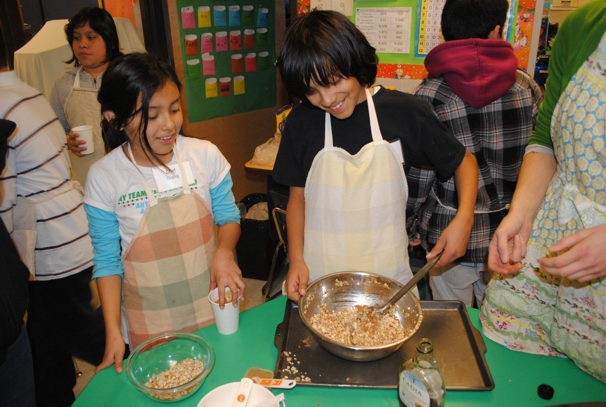 2 students stirring food in a bowl
