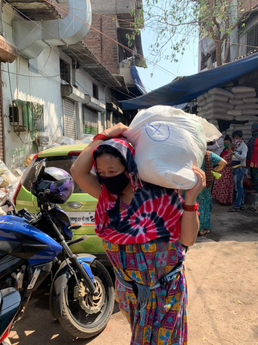 A woman in the area carries her newly acquired supplies home