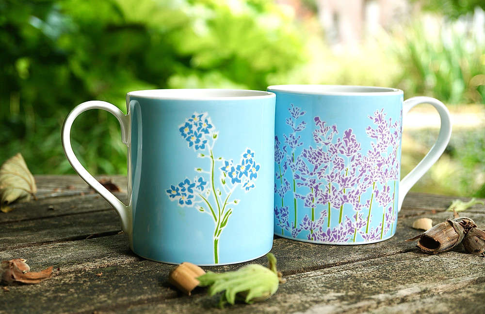 Forget me not mug and Lavender mug on a table in the garden