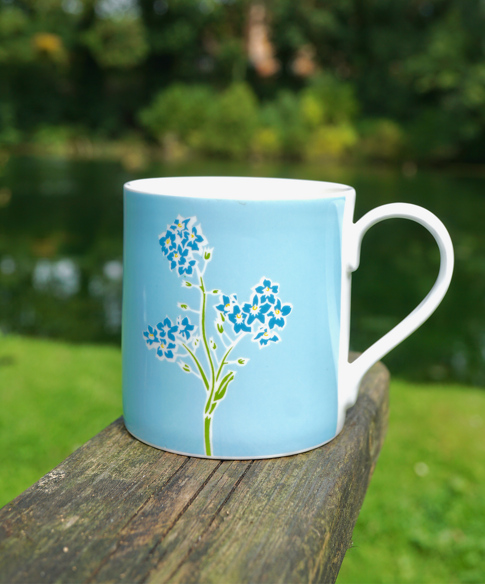 Forget me not mug on wooden bench in the garden