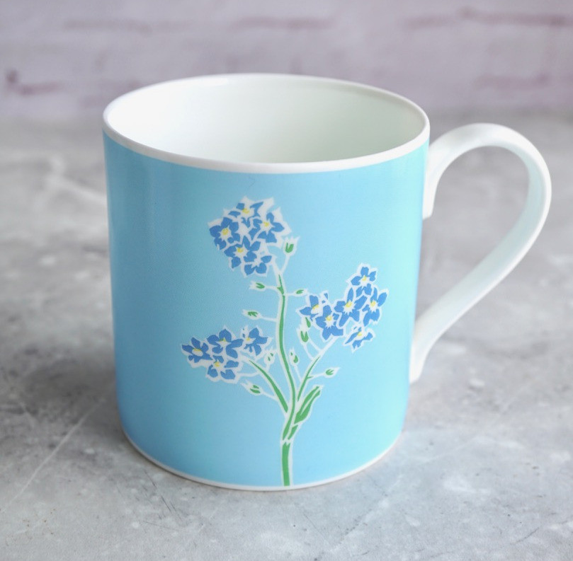 A mug featuring blue forget me not flowers on a pale blue background