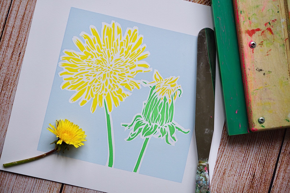 An art print of a yellow dandelion on a blue background