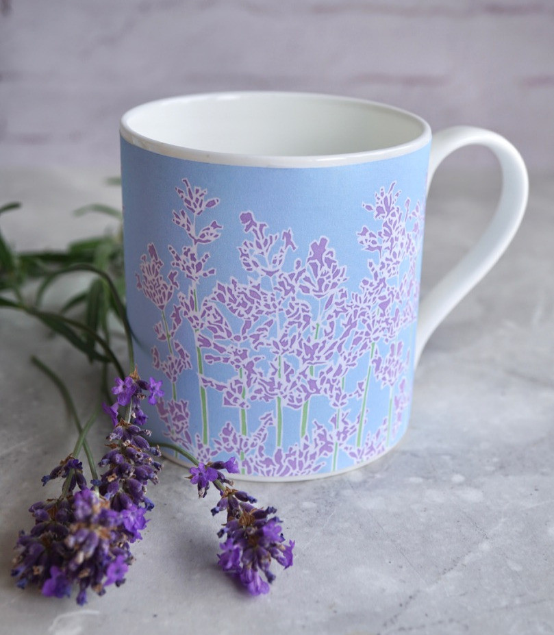 A china mug featuring purple lavender flowers against a pale blue background