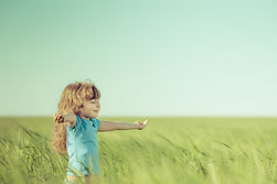 Happy child in spring field. Young girl