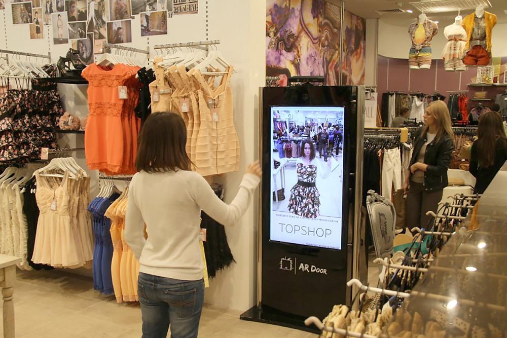 Mulher compra em toten dentro da loja usando provador virtual