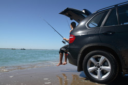 Fishing from a car by the beach