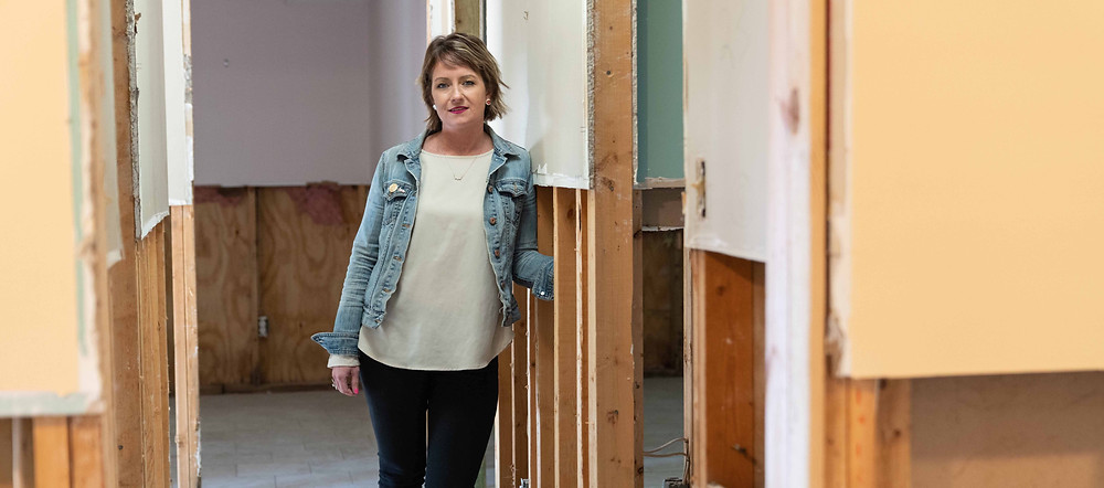 Woman rebuilding home after flood damage from a hurricane.