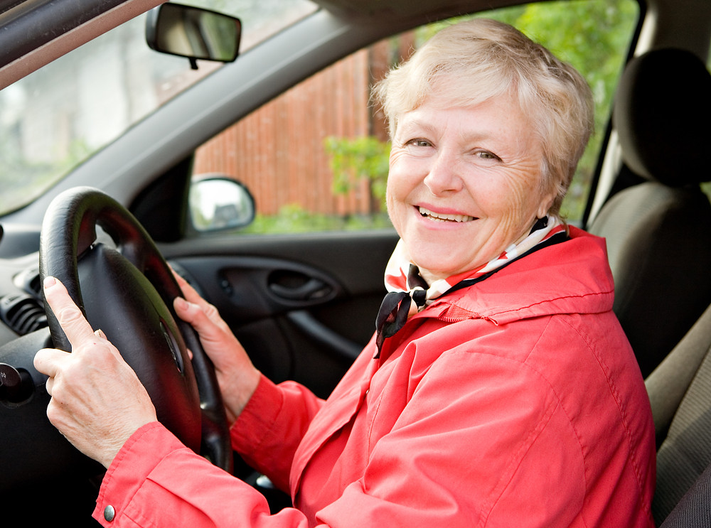 Smiling Senior Driving with Auto-Owners Insurance Company and with all the discounts