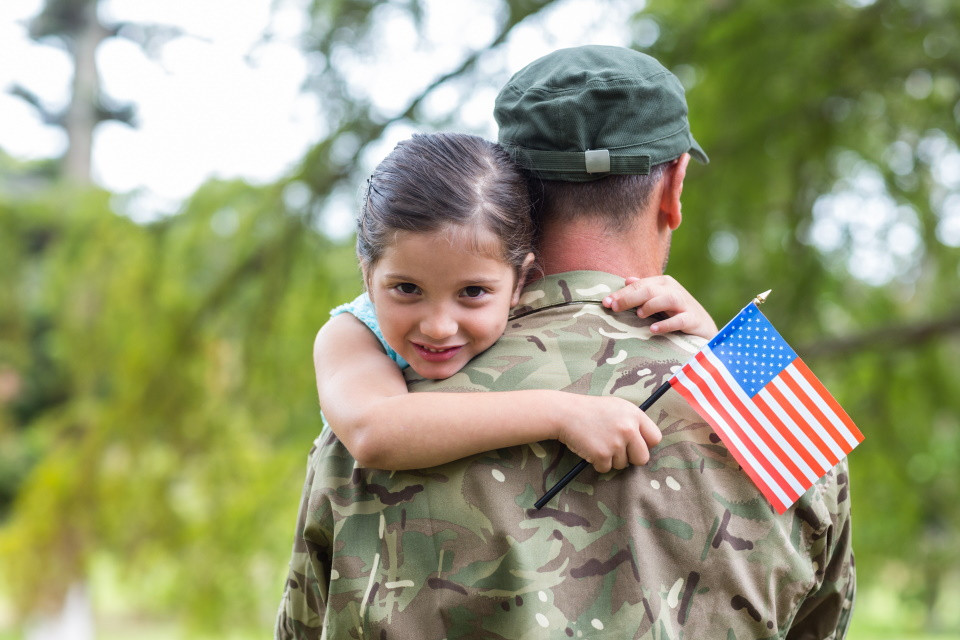 Boy hugging dad, in military service with flag
