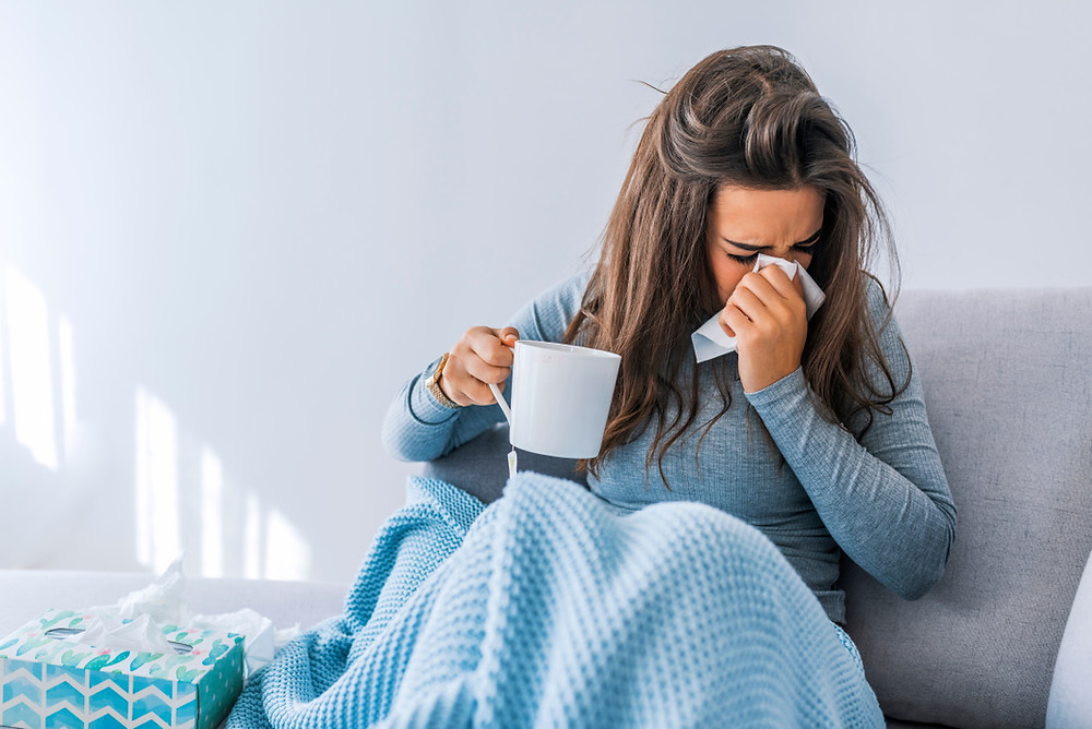 Picture of sick woman not sure if she has a cold, flu, or COVID19