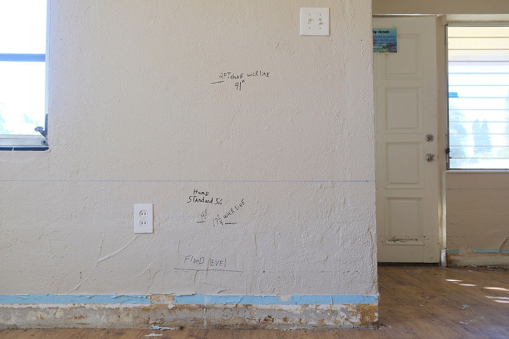 Madeira Beach, Florida USA - January 5 2021: Water remediation elevations drawn on a wall of a home flooded by tropical storm ETA as it slammed the Tampa Bay region. Total demolition is scheduled.