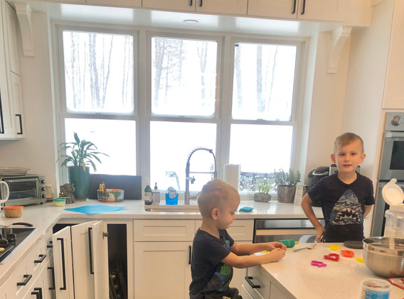 """The girls are such """"helpers"""" in the kitchen.  Today, they were on clean up while Drew and Reid made cookies. 😊"""