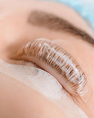 Young woman undergoing procedure of eyelashes lamination in beauty salon, closeup.jpg
