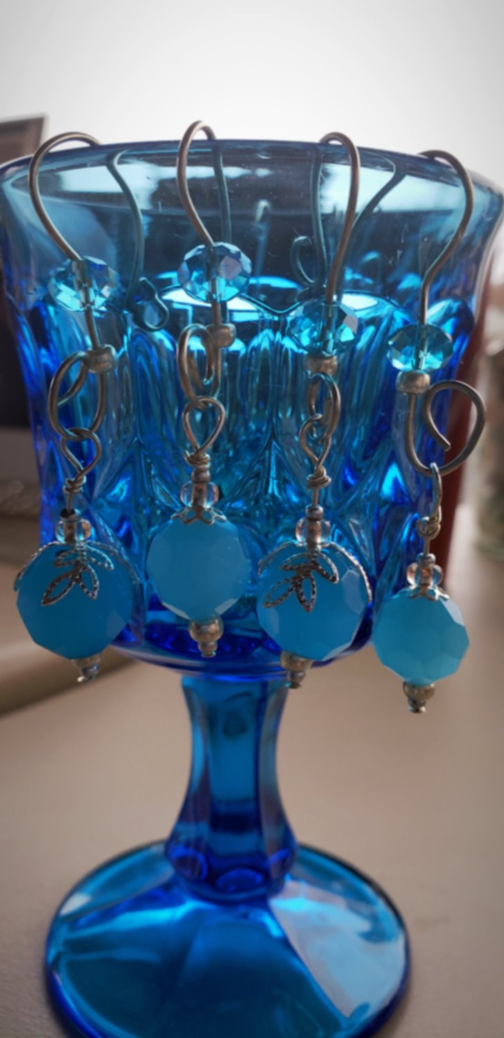 a blue wine glass with beaded ornaments