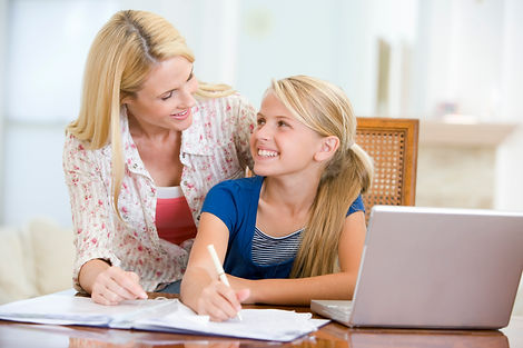 Woman-helping-young-girl-do-homework-in-
