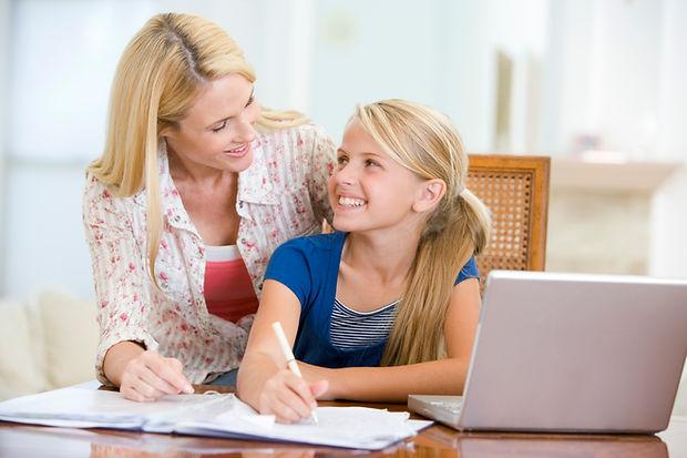 Woman-helping-young-girl-do-homework-in-