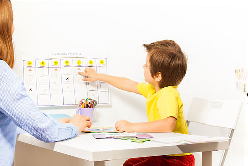 Boy-points-at-activities-on-calendar-learning-days-475663916_5192x3472.jpeg