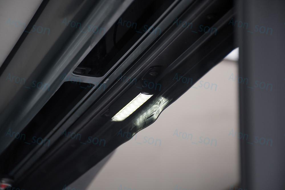 Ajtótér megvilágító lámpa, szokatlan helyen. Az ajtólapok záródásakor épphogy 'van helye'.