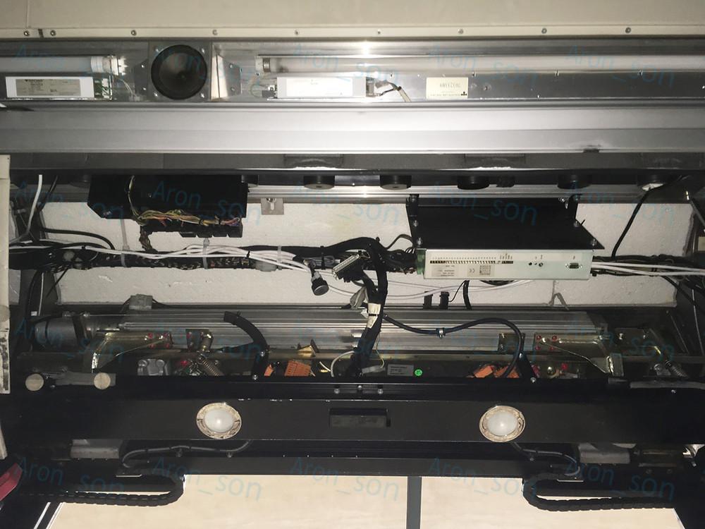 Egy Webasto-Kiekert gyártmányú rendszer mechanikája + elektronikája. (A képen lefelé vannak az ajtólapok.) <br />Az ajtó környéki teret megvilágító spotlámpák felett a szürkés, hosszú elem a 'hajtást' rejti.